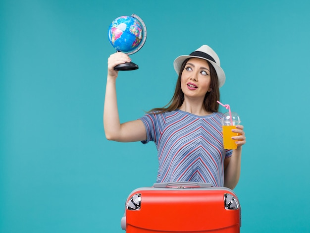 Vue de face femme en vacances tenant le jus et le globe sur le plancher bleu mer voyage voyage vacances été voyage
