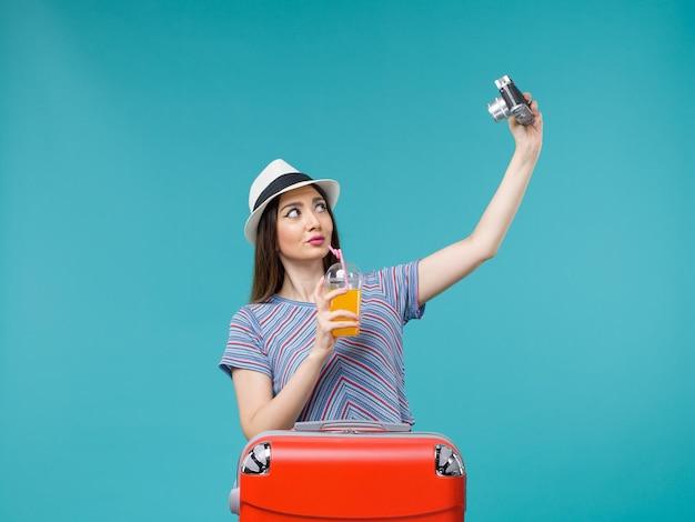 Vue de face femme en vacances tenant le jus et prendre des photos avec appareil photo sur fond bleu voyage été voyage vacances mer voyage