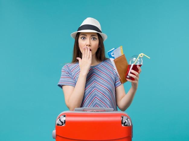 Vue de face femme en vacances tenant le portefeuille avec des billets sur le fond bleu voyage voyage femme été avion de mer