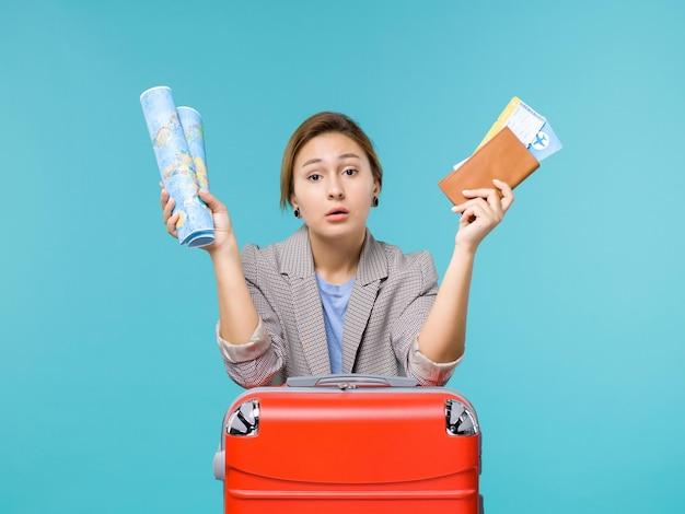 Vue de face femme en vacances tenant le portefeuille de la carte et les billets sur le fond bleu avion voyage mer voyage vacances