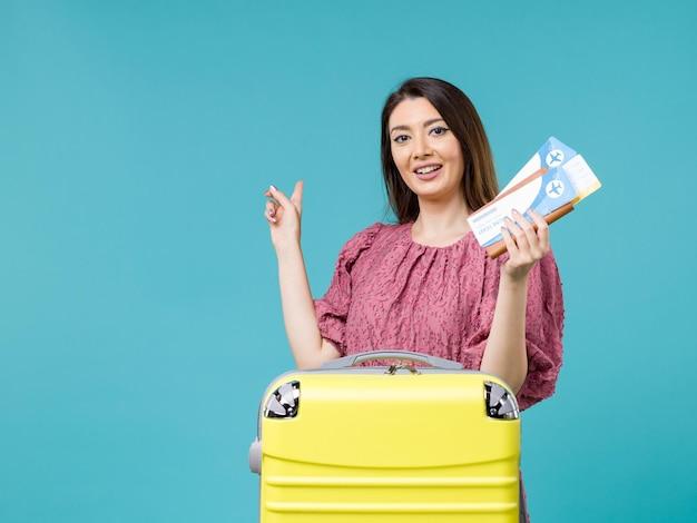 Vue de face femme en vacances tenant ses billets sur fond bleu clair voyage été voyage femme vacances mer