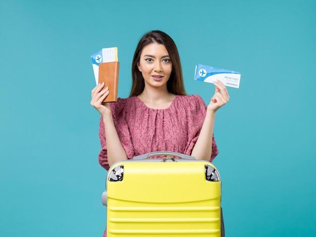 Vue de face femme en vacances tenant ses billets sur le fond bleu voyage mer femme voyage vacances été