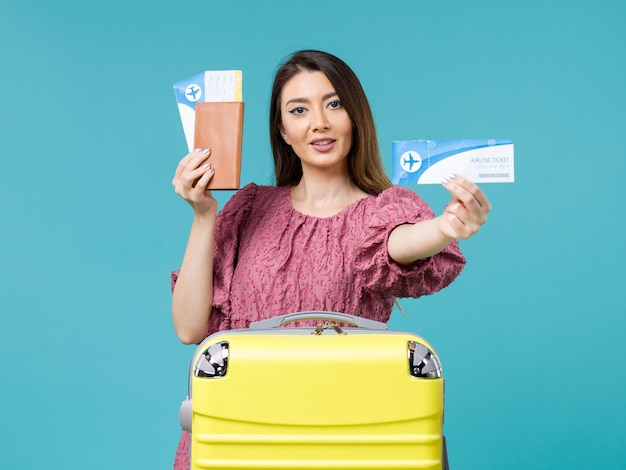 Vue de face femme en vacances tenant ses billets sur fond bleu voyage mer voyage vacances femme été