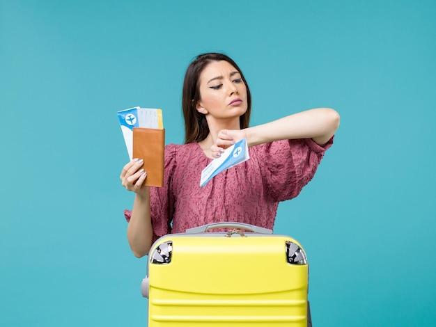 Vue de face femme en vacances tenant ses billets et vérifier l'heure sur fond bleu voyage mer voyage vacances femme été