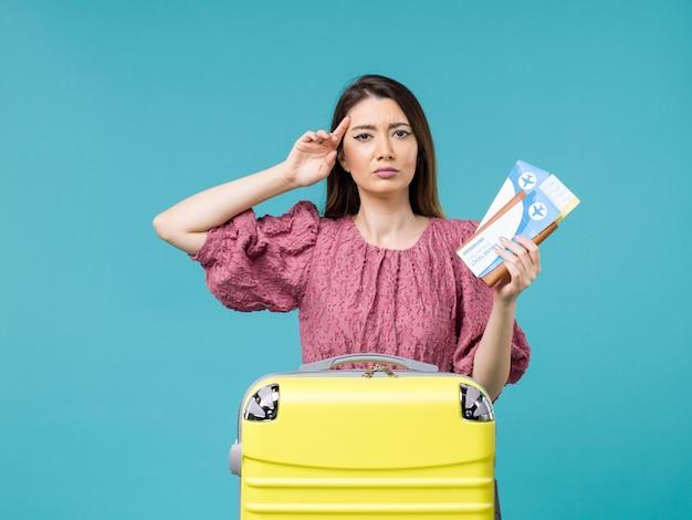 Vue de face femme en vacances tenant ses billets sur le voyage de bureau bleu voyage d'été femme vacances à la mer