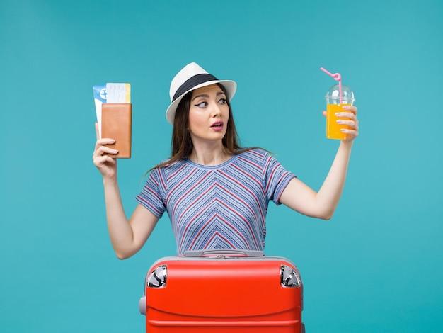 Vue de face femme en vacances tenant son jus et billets sur fond bleu clair voyage été mer voyage voyage vacances