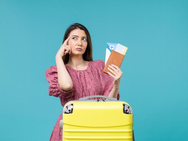 Vue de face femme en vacances tenant son portefeuille et billets sur fond bleu voyage vacances voyage femme été mer