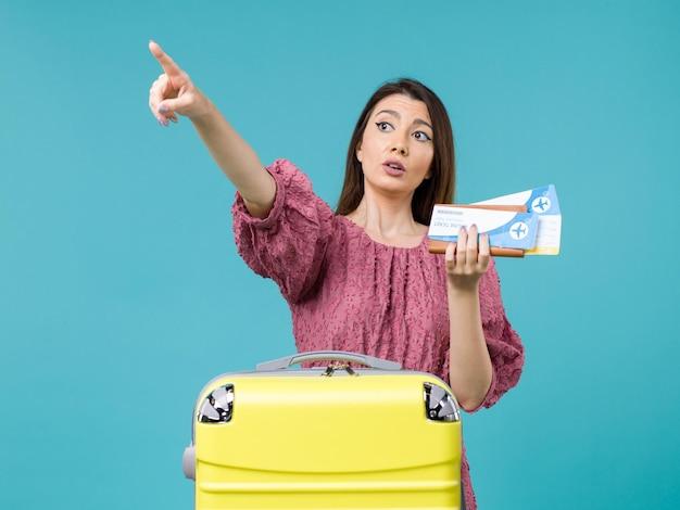 Vue de face femme en vacances tenant son portefeuille et billets pointant quelque part sur fond bleu voyage femme voyage d'été vacances à la mer