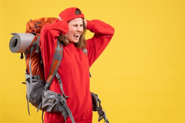Vue de face femme voyageur en colère en sac à dos rouge tenant la tête hurlant