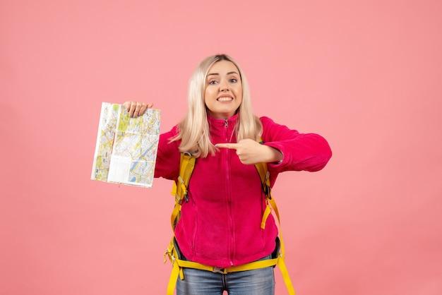 Vue de face femme voyageur dans des vêtements décontractés portant sac à dos pointant sur la carte