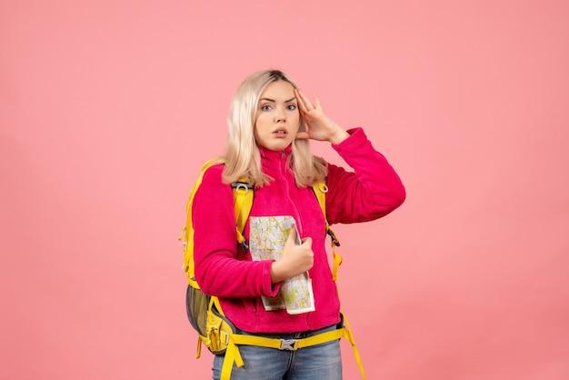Vue de face femme voyageur dans des vêtements décontractés et sac à dos tenant la carte