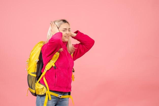 Vue de face femme voyageur en difficulté avec sac à dos tenant ses oreilles