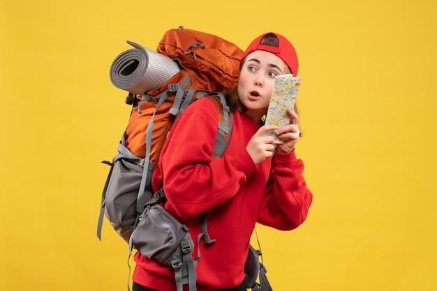 Vue de face femme voyageur intéressé avec sac à dos tenant la carte en regardant quelque chose