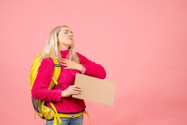 Vue de face femme voyageur avec sac à dos mettant la main sur sa poitrine tenant le carton