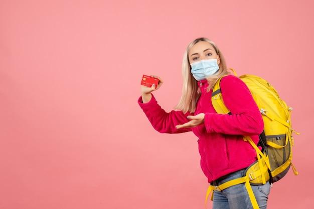 Vue de face femme voyageur avec sac à dos portant masque tenant la carte