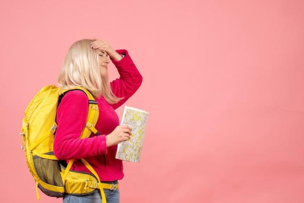 Vue de face femme voyageur avec sac à dos tenant la carte mettant la main sur sa tête