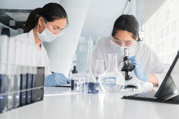 Vue de face des femmes asiatiques travaillant ensemble sur un projet chimique