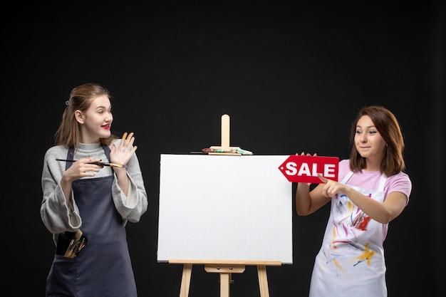 Vue de face de femmes peintres avec chevalet tenant une bannière de vente sur un mur sombre