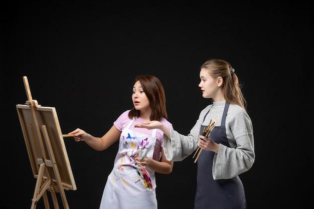 Vue de face femmes peintres dessin sur chevalet sur le mur noir couleur dessiner travail peinture art photo artiste photo