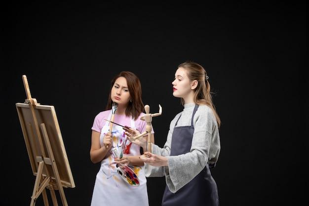Vue de face femmes peintres dessin sur chevalet sur mur noir couleurs dessiner peinture travail art photo artiste photo