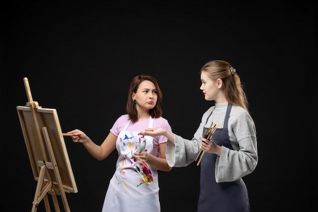 Vue de face femmes peintres dessin sur chevalet sur mur noir tirage couleur peinture travail art photo artiste photos