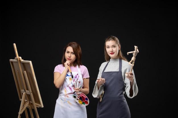 Vue de face femmes peintres dessin image de figure humaine sur chevalet sur le mur noir dessiner peinture art photo artiste couleur travail photo