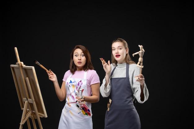 Vue de face femmes peintres dessin image de figure humaine sur chevalet sur mur noir dessiner peinture art photo artiste photo couleur