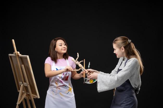 Vue de face femmes peintres dessin photo de figure humaine sur chevalet sur mur noir dessiner peinture art artiste couleurs travail photo photo