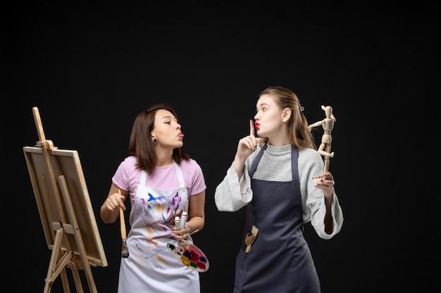 Vue de face femmes peintres dessin photo de figure humaine sur chevalet sur mur noir dessiner peinture art photos artiste couleur travail photo