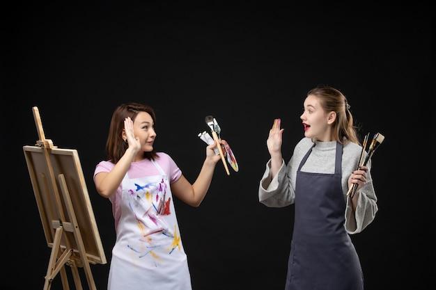 Vue de face femmes peintres tenant des peintures et des glands pour dessiner acclamant le mur noir dessiner travail photo art photo couleur peinture artiste