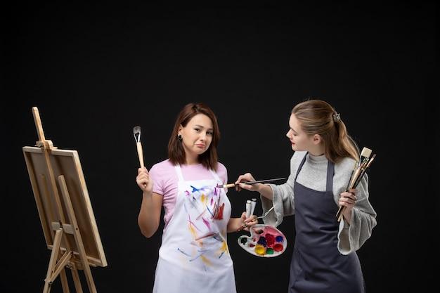 Vue de face femmes peintres tenant des peintures et des glands pour dessiner sur le mur noir dessiner travail de peinture photo art photo couleur artiste