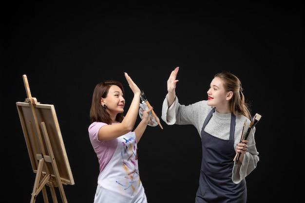 Vue de face femmes peintres tenant des peintures et des glands pour dessiner sur un mur noir dessiner travail photo art couleurs photo peinture artiste