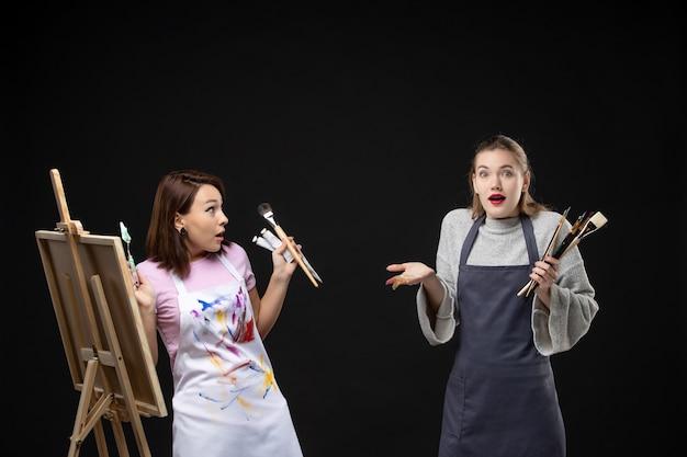 Vue de face femmes peintres tenant des peintures et des glands pour dessiner sur le mur noir photo art artiste couleur travail photo dessiner peinture