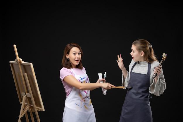 Vue de face des femmes peintres tenant des peintures et des glands pour dessiner sur un mur noir photo couleur dessiner des photos d'emploi art peinture artiste