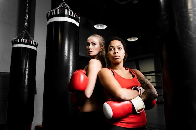 Vue de face des femmes posant ensemble dans un centre d'entraînement de boxe
