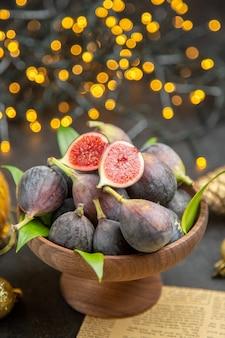 Vue de face des figues fraîches autour des jouets de noël sur un fond sombre photo de noël au goût sombre des fruits