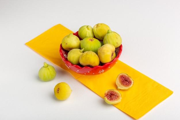 Vue de face figues fraîches délicieux fœtus doux à l'intérieur de la plaque rouge sur la surface blanche