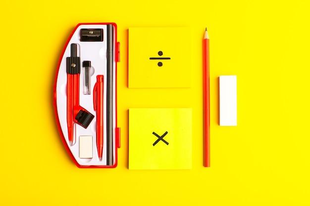 Vue de face des figures géométriques avec des autocollants et un crayon sur une surface jaune