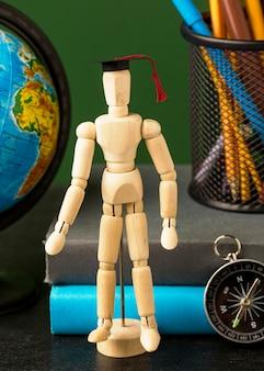 Vue de face de la figurine en bois avec capuchon académique et crayons