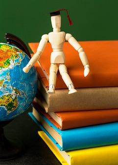 Vue de face de la figurine en bois avec capuchon académique sur les livres et globe