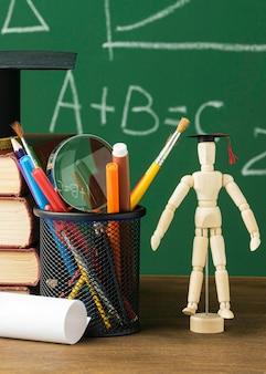 Vue de face de la figurine en bois avec capuchon académique et livres