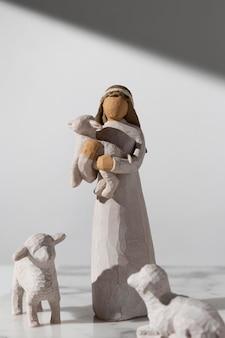 Vue de face de la figurine féminine du jour de l'épiphanie avec des moutons