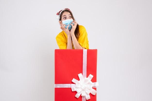 Vue de face fille agitée avec bonnet de noel debout derrière un grand cadeau de noël