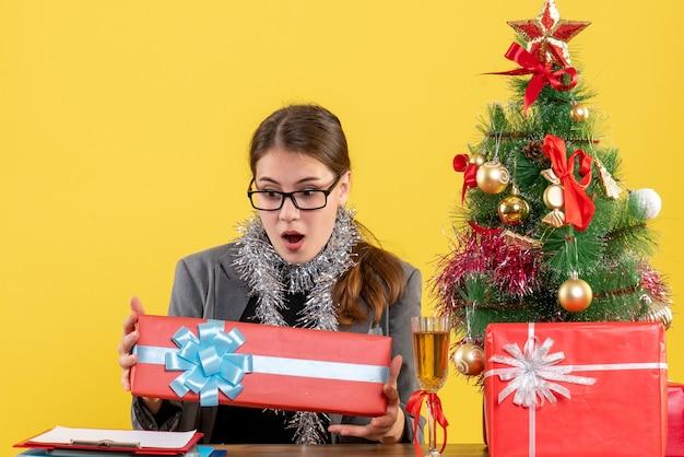 Vue de face fille aux yeux écarquillés avec des lunettes assis à la table en regardant son arbre de noël cadeau et cocktail de cadeaux