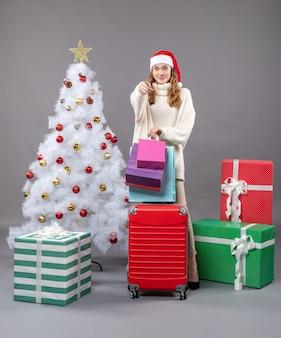 Vue de face fille blonde avec bonnet de noel tenant valise rouge et sacs à provisions arbre de noël blanc
