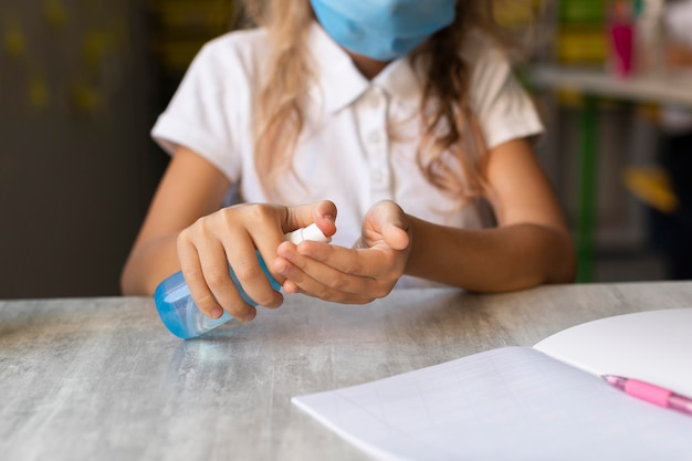 Vue de face fille blonde désinfectant ses mains
