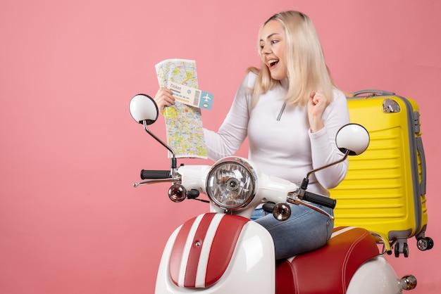Vue de face fille blonde heureuse sur cyclomoteur tenant le billet et la carte