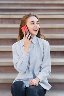 Vue de face fille blonde parlant au téléphone