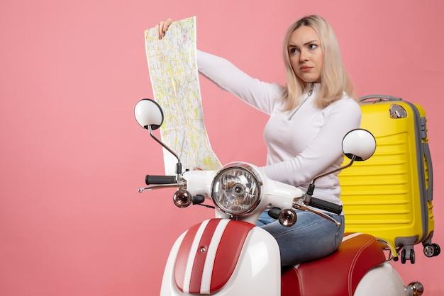 Vue de face fille blonde sérieuse sur cyclomoteur en regardant la carte