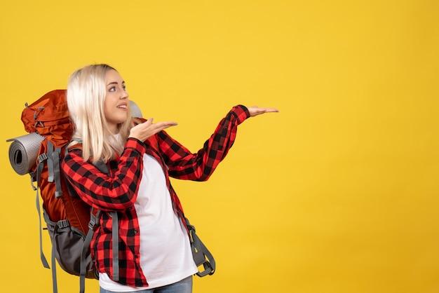 Vue de face fille blonde avec son sac à dos montrant quelque chose